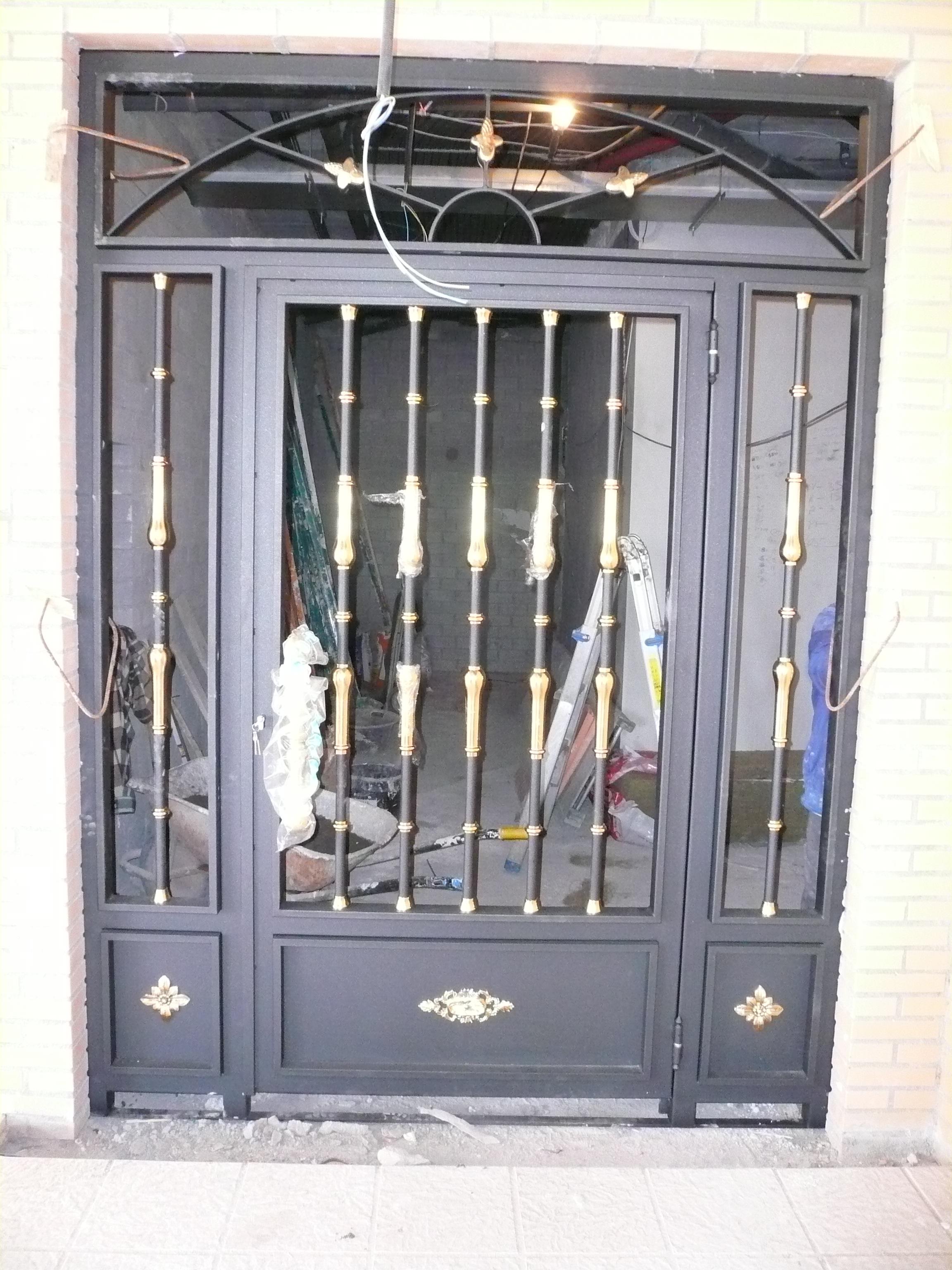 Vista puerta de portal de forja Edificios Los Alisos